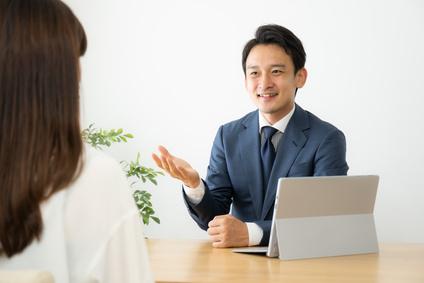 保険セールスマンの説明を聞く女性の画像