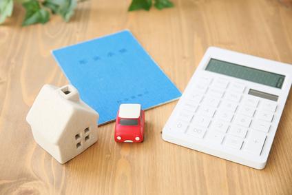 家と車と年金手帳と電卓の画像